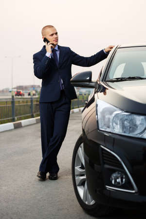 Young businessman calling on the phone at the car