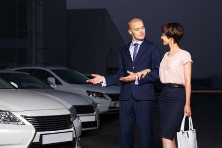 Pareja joven que recoge el nuevo coche en el lote concesionario