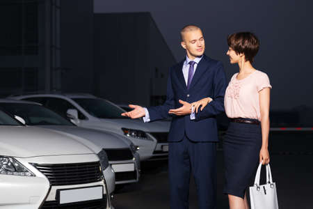 Young couple collecting new car at dealership lot photo