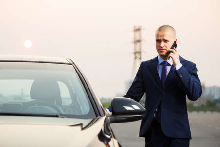 Young businessman calling on the phone at the car photo