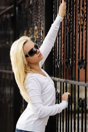 Blond woman at the cast iron fence photo