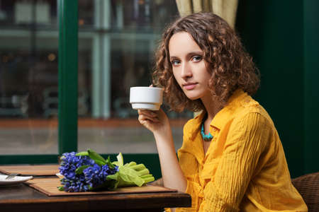 Sad young woman drinking tea at restaurant Stock Photo - 23176005