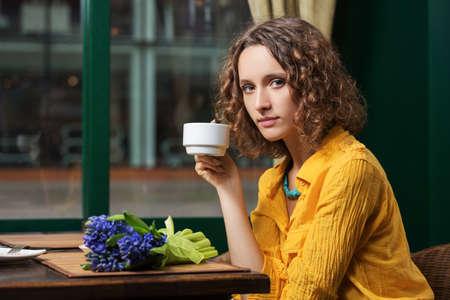 Sad young woman drinking tea at restaurant Stock Photo - 23176005