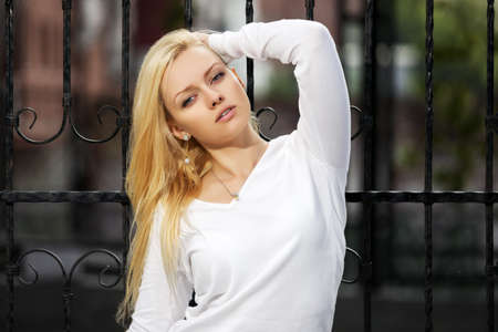 Blond woman at the cast iron fence Stock Photo - 23176077