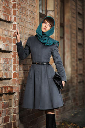 Sad young woman in grey classic coat at the wall Stock Photo - 23176158