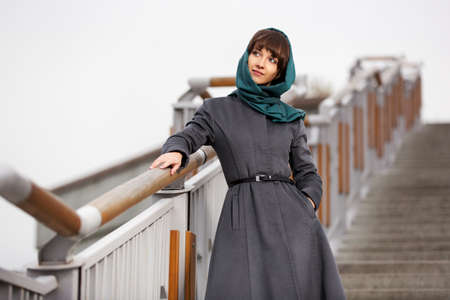 Happy young woman in grey classic coat on the steps Stock Photo - 23176155