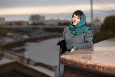 Happy young woman in classic coat on the urban background photo