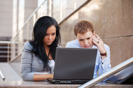 college building: Young business couple using laptop
