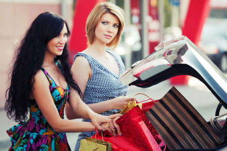 Two young women with shopping bags at the car photo