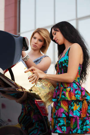 Young women loading shopping bags in a car trunk photo