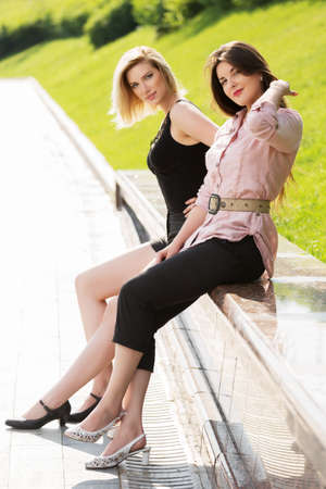 Two happy women sitting on the bench in a city park photo