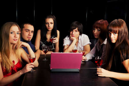 Young people using laptop in a night bar photo