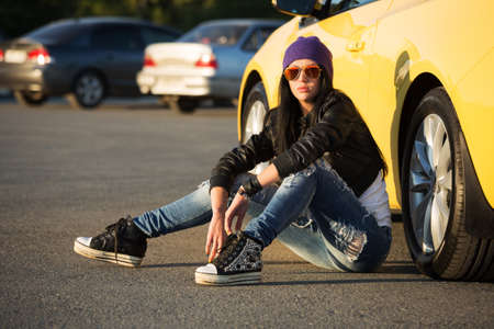 Fashionable punk woman sitting on the car parking photo