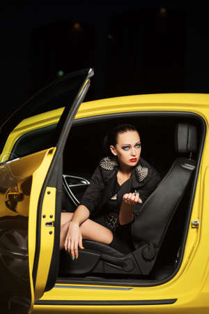 Fashionable woman smoking a cigarette in a car photo