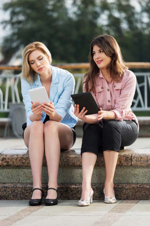 Two young women holding a digital tablet computers photo