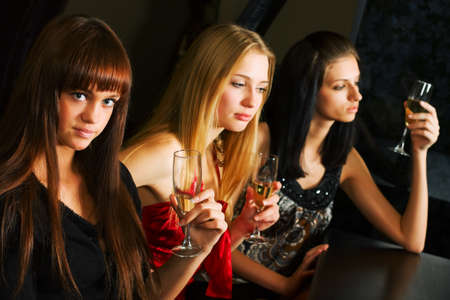 Young women drinking champagne in a night bar photo