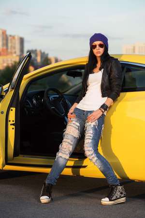 Fashionable punk woman standing at the car photo