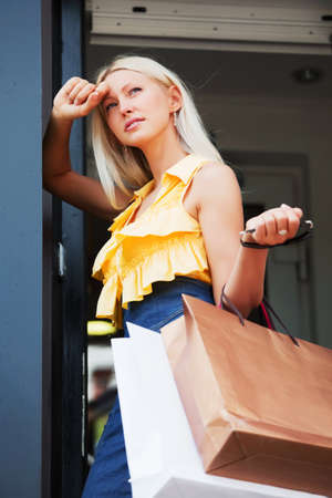 Sad blond woman with shopping bags  photo