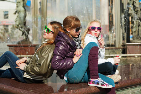 cool girl: Teenage girls relaxing against a city fountain Stock Photo