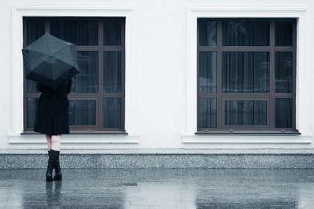mur noir: Femme avec le parapluie sous la pluie
