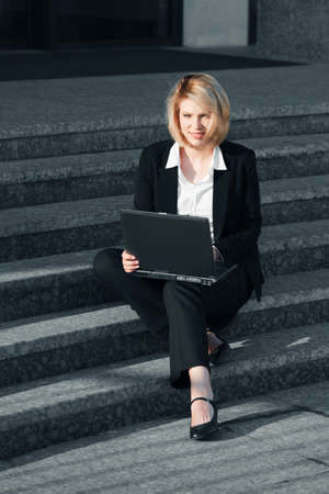 Young business woman using laptop on the steps photo