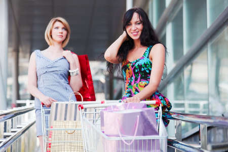 Young women with shopping cart photo
