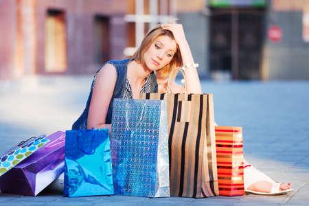sidewalk sale: Sad young woman sitting among a shopping bags Stock Photo
