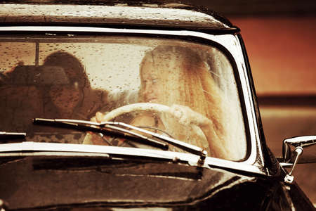 Young woman driving retro car in the rain photo