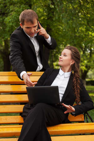 Young business people using laptop in a city park photo