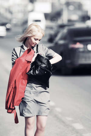 Young blond woman walking on a city street photo