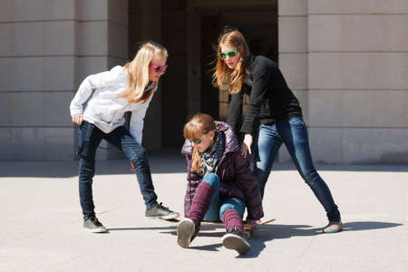 Teenage girls playing with skateboard photo