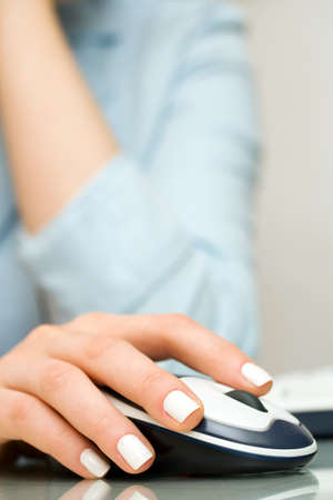 Female hand using computer mouse photo