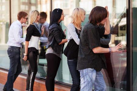 Jongeren kijken door het winkelcentrum raam