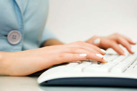 Female hands typing on computer keyboard photo
