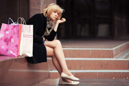 Sad young woman with shopping bags  photo