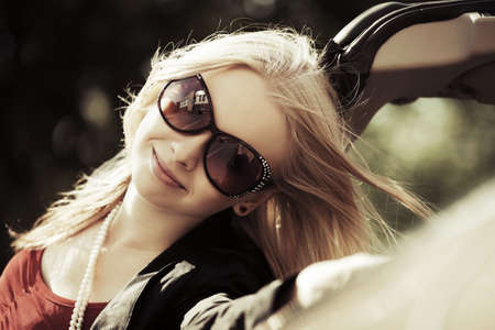 Happy young blond woman at the convertible car photo