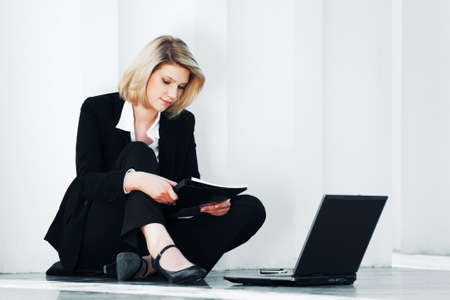 Young business woman using laptop at the wall photo