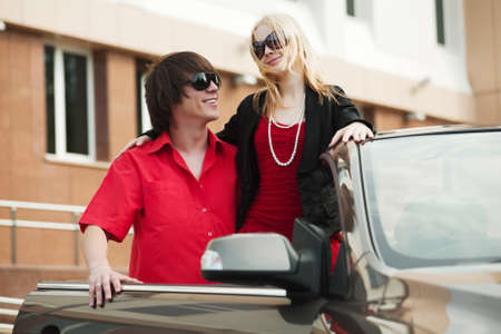 Happy young couple at the car photo