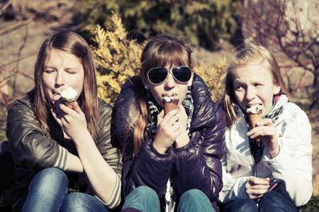 Teenage girls eating an ice cream photo