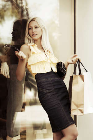 clothing store: Young fashion woman with shopping bags at the mall window