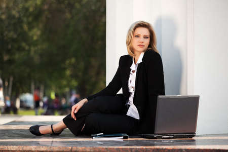 Young business woman with laptop sitting at the wall photo