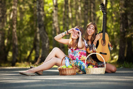 Two hippie girls with guitar in a summer forest photo