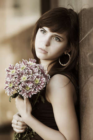 Sad young woman with a flowers at the wall  photo