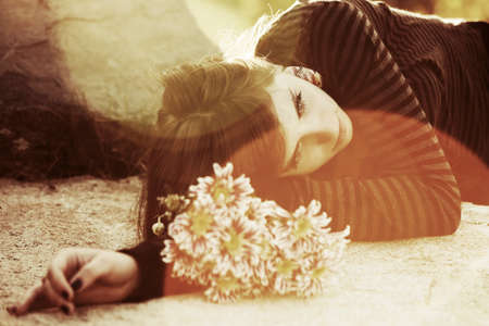 lonely woman: Sad young woman lying on the tombstone