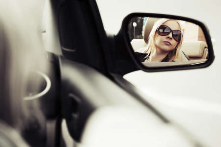 Blond woman looking in the car mirror photo