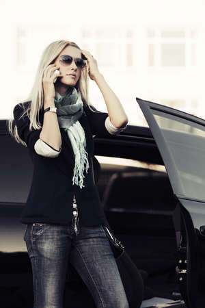 Fashion business woman calling on the phone at the car  photo