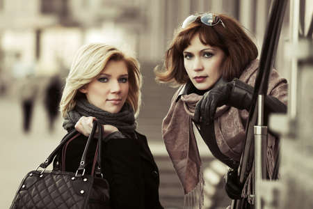 Two happy young fashion women on the city street photo