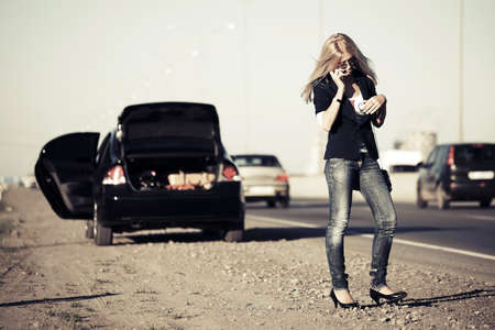 calling for help: Young fashion woman with broken car calling for help