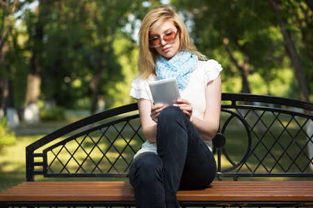 e book reader: Young fashion woman using tablet computer in a city park