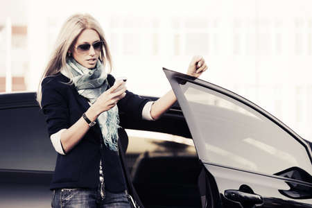 Fashion business woman calling on the phone at the car Foto de archivo